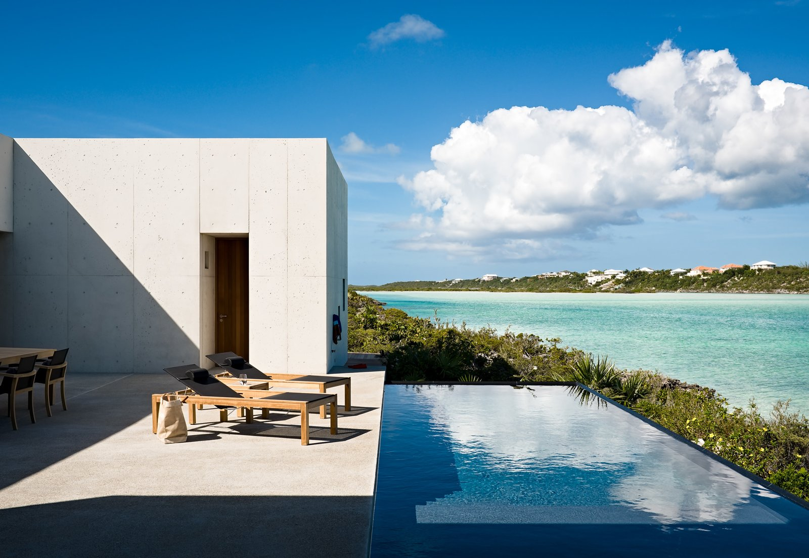 Outdoor, Back Yard, Shrubs, Large, Concrete, Small, Concrete, and Infinity Outside, a shallow pool cuts a line between the coastline and the adjoining terrace, bringing the expanse of ocean water closer to the living spaces.  Best Outdoor Shrubs Infinity Photos from A Rick Joy–Designed Retreat in the Caribbean Encourages an Easy-Breezy State of Mind