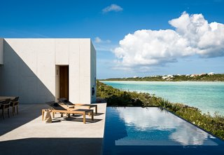 Outside, a shallow pool cuts a line between the coastline and the adjoining terrace, bringing the expanse of ocean water closer to the living spaces.