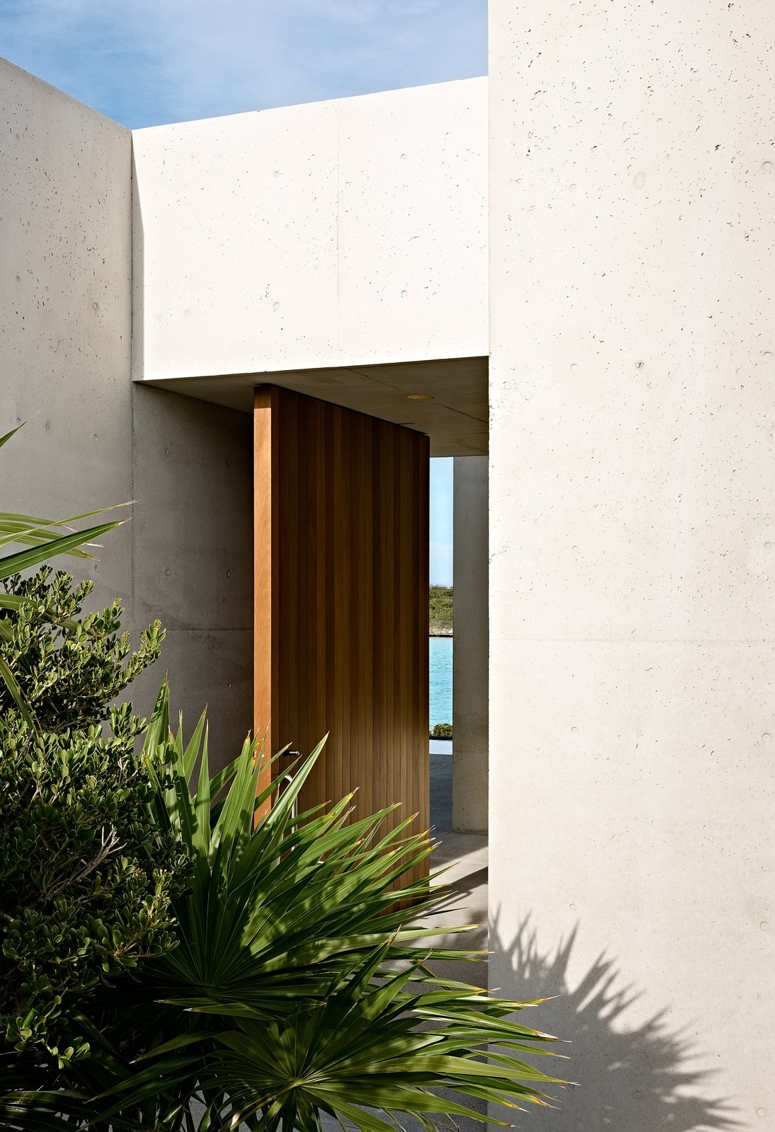 Doors, Swing Door Type, Exterior, and Wood An oversized mahogany door provides a grand entrance to the complex.  Photos from A Rick Joy–Designed Retreat in the Caribbean Encourages an Easy-Breezy State of Mind