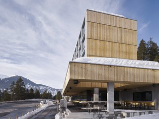 The individual modules are emphasized by metal siding; the rest of the building has been constructed from vertical slats of rough-cut, untreated larch.