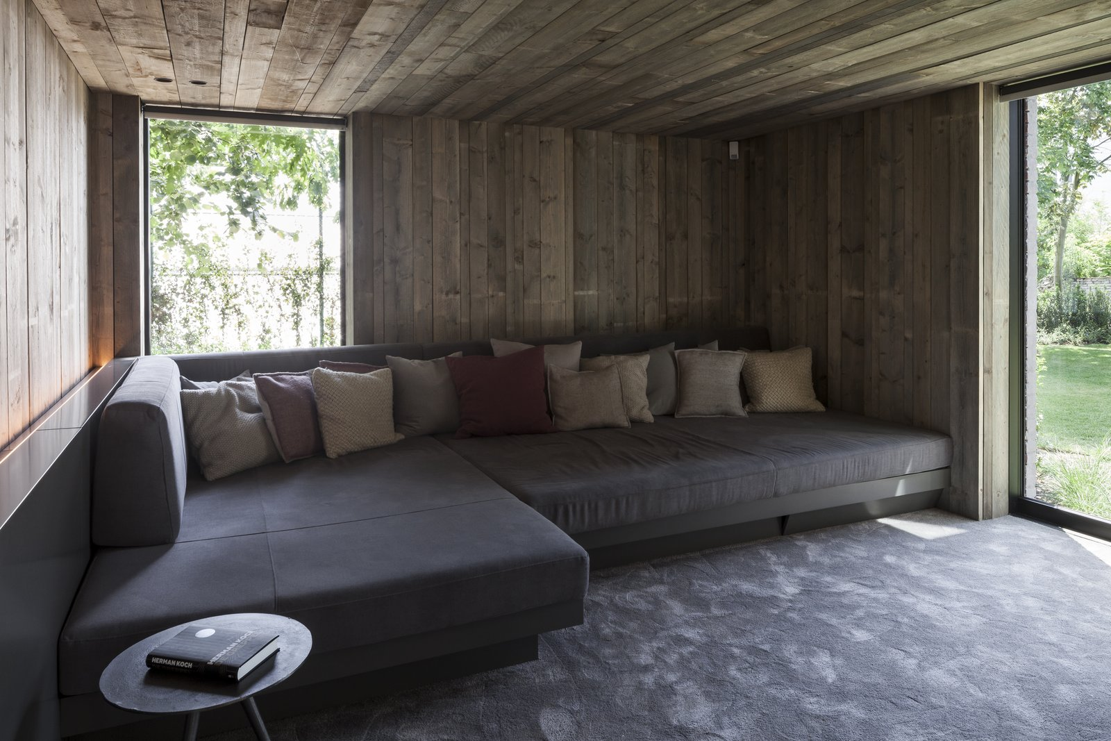 Shed & Studio, Den, and Family Room The garden's former wartime bunker has been connected to the property and transformed into a cozy, wood-clad media room.  Shed & Studio Family Room Photos from This Glass Pied-à-Terre Is Hidden in a Belgian Garden