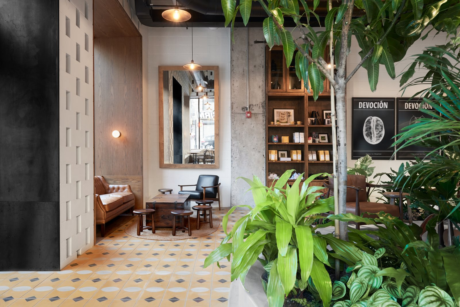 Dining Room, Pendant Lighting, Cement Tile Floor, Table, Chair, Wall Lighting, Stools, and Shelves The space offers several nooks for quiet moments.    Photo 6 of 10 in This New Brooklyn Cafe Is Brewing Up More Than Tasty Artisanal Coffee