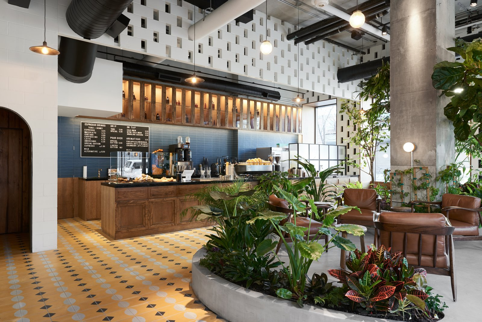 Dining Room, Chair, Cement Tile Floor, Pendant Lighting, Bar, Wall Lighting, and Concrete Floor The diverse material palette includes Colombian wood, concrete blocks, tiles, and stone.  Photo 3 of 10 in This New Brooklyn Cafe Is Brewing Up More Than Tasty Artisanal Coffee