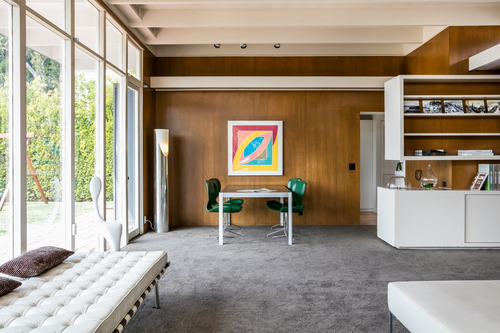 Living, Chair, Ottomans, Table, Carpet, Storage, Track, Bench, and Floor Original wood paneling lines the walls.  Living Storage Table Ottomans Photos from Case Study House #18 in L.A. Hits the Market at $10M and Includes Plans From Tom Kundig