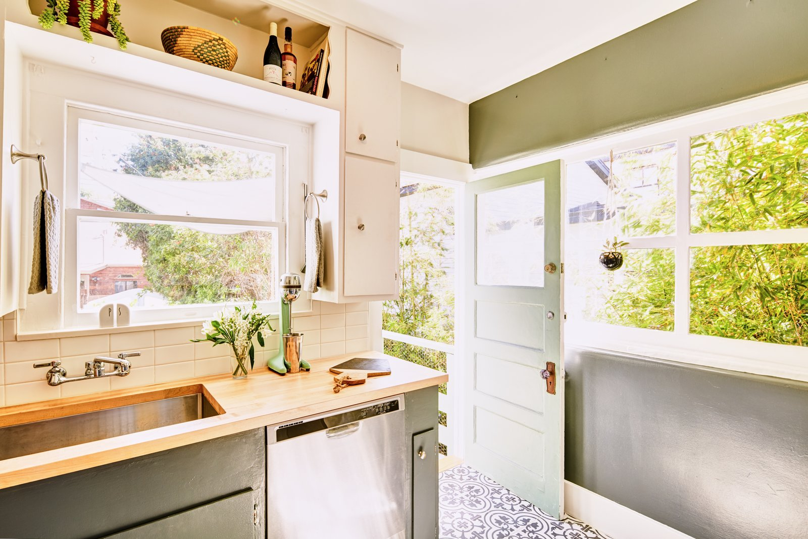 Kitchen, Cement Tile, Dishwasher, Wood, Colorful, Subway Tile, Undermount, and White Thanks to the ample natural light, the kitchen area maintains a warm brightness.    Best Kitchen White Cement Tile Photos from An Original Venice Craftsman With a Primetime Pedigree Is Listed For $2.75M