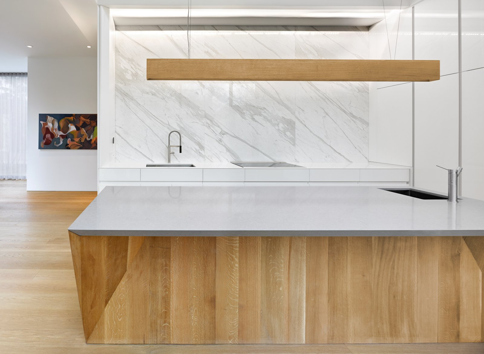 Kitchen, Marble Counter, Marble Backsplashe, Light Hardwood Floor, Undermount Sink, Pendant Lighting, Cooktops, White Cabinet, and Wood Cabinet Calacatta marble slabs are meticulously detailed to reflect the surrounding landscape and contrast the heavy, flat-sawn solid oak island with a faceted base.     Photo 6 of 12 in This Award-Winning Home in Canada Allows Two Generations to Live Under One Roof