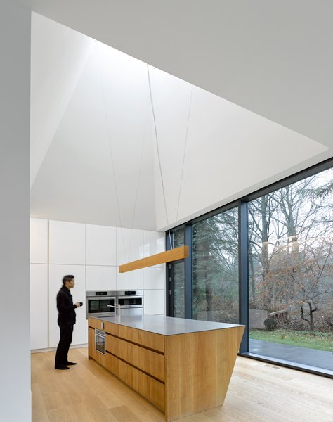 The kitchen anchors the south end of the home. Set in a double-height volume, the 20-foot-tall pyramidal ceiling creates an expansive space that opens to the creek, the courtyard, and above to the sky.