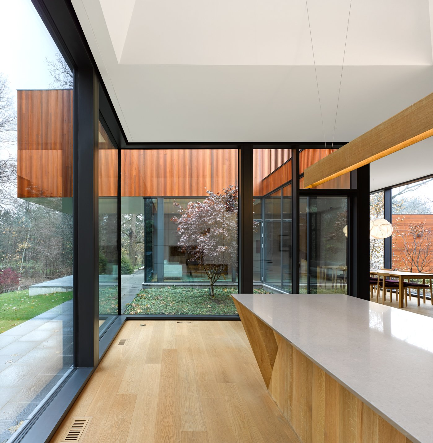 Kitchen, Light Hardwood Floor, Marble Counter, Wood Cabinet, and Pendant Lighting Angular geometry and a minimalist touch define the contemporary aesthetic of the residence.    Photo 5 of 12 in This Award-Winning Home in Canada Allows Two Generations to Live Under One Roof