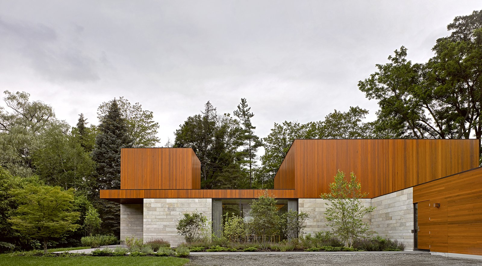 Exterior, Flat RoofLine, House Building Type, Wood Siding Material, and Stone Siding Material The exterior is a mix of wood and stone, and the ground floor is clad in locally-quarried Algonquin limestone around the perimeter.     Photo 11 of 12 in This Award-Winning Home in Canada Allows Two Generations to Live Under One Roof