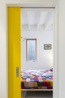 A guest room is tucked behind a primary yellow pocket door on the ground floor.