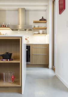 The kitchen features white quartz counters, a mounted induction cooktop, and a full-height backsplash with white penny-round tiles.
