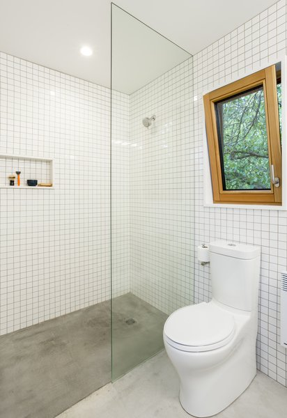 The bathrooms feature simple white tiles with concrete floors, while pocket doors throughout the home are painted in primary colors to create a subtle pop of bright color.