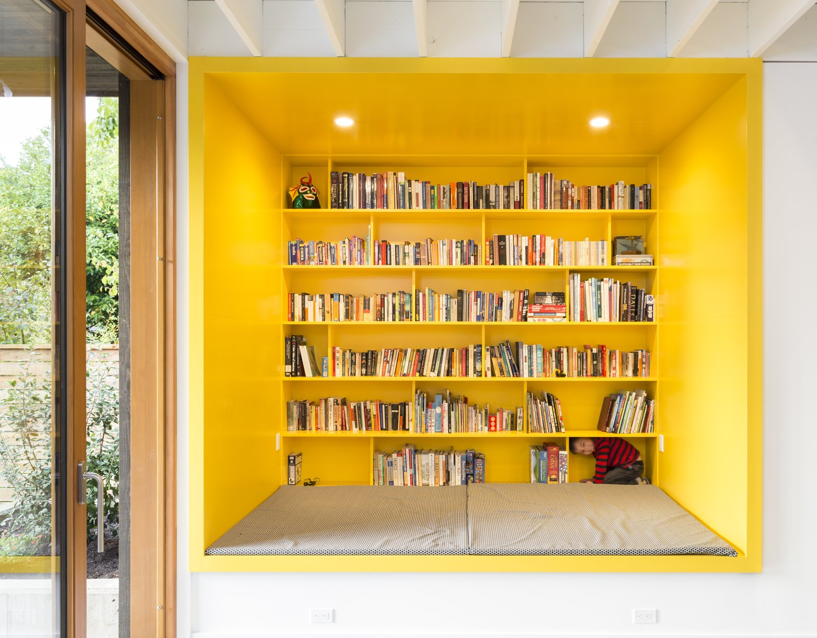 Living Room, Shelves, Bench, Recessed Lighting, and Bookcase Thanks to a spacious bookshelf and plenty of seating, this vibrant area is an inviting spot to read and relax.    Best Photos from A Bright Yellow Reading Nook Steals the Show in This Energy-Efficient Portland Abode