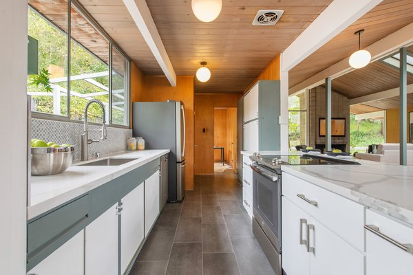 Tasteful contemporary updates have been added, including a renovated kitchen with composite countertops, stainless steel appliances, a new electric cooktop, new tile backsplash, and ample cabinet space.
