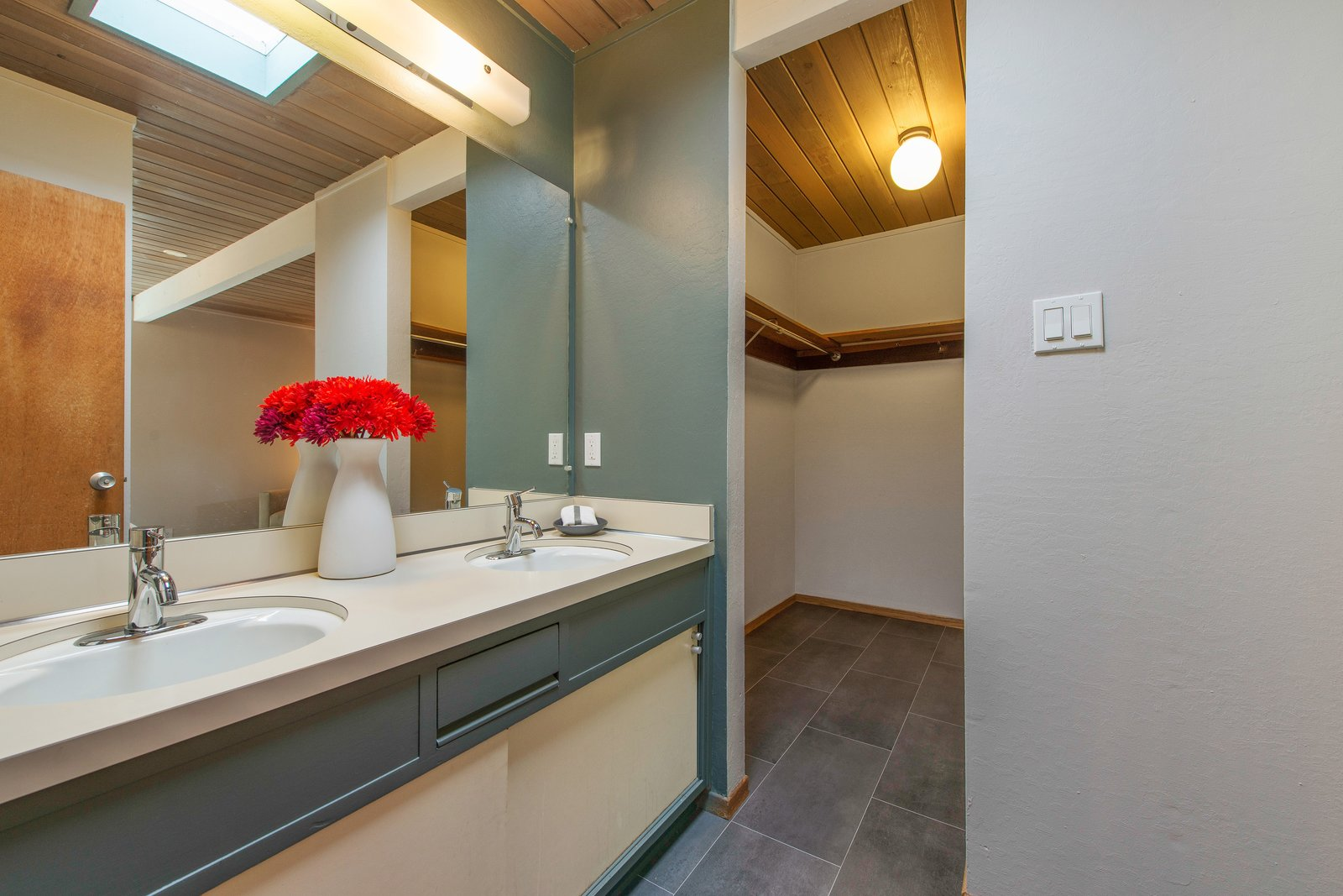 Bath Room, Wall Lighting, Drop In Sink, Laminate Floor, Laminate Counter, and Ceiling Lighting  The master bedroom also has an en-suite bathroom and features a large walk-in closet.     Photo 9 of 14 in Live Large in This Extra-Spacious Eichler That's Asking $1.38M