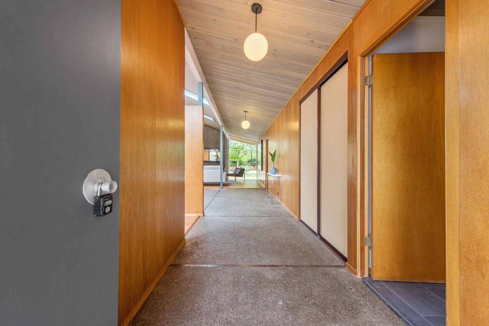 Hallway and Concrete Floor A corridor leads from the entrance to the open-plan living space. Note the original aggregate concrete flooring.     Photo 1 of 14 in Live Large in This Extra-Spacious Eichler That's Asking $1.38M