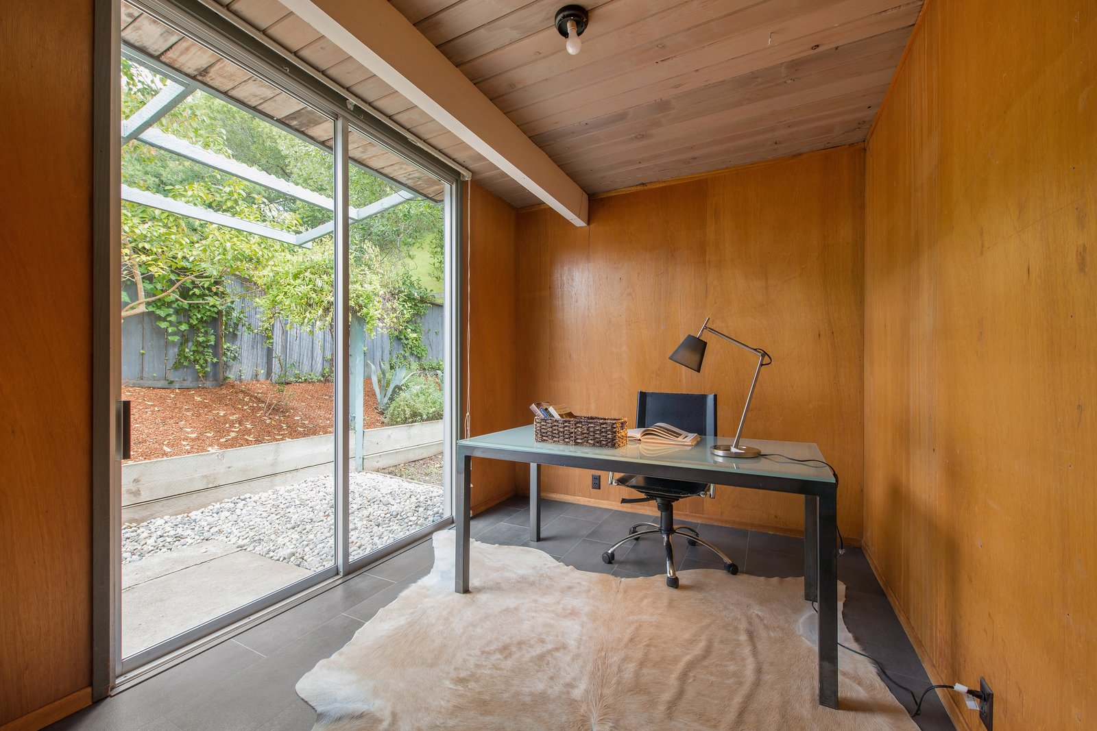 Office, Study, Desk, Laminate, Chair, Rug, and Lamps This is the bonus office space that is complete with original wood paneled walls and a sliding door to the patio.     Office Study Laminate Photos from Live Large in This Extra-Spacious Eichler That's Asking $1.38M