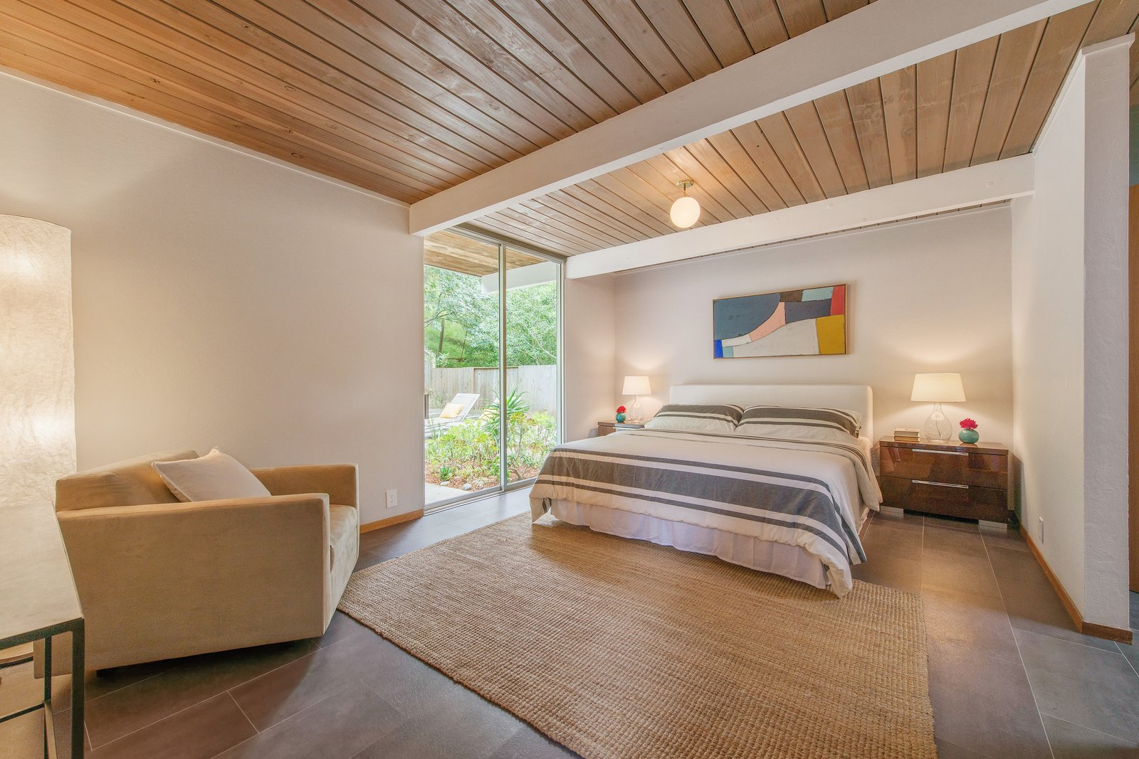 Bedroom, Bed, Night Stands, Laminate Floor, Rug Floor, Table Lighting, Ceiling Lighting, and Chair The master bedroom offers tremendous space, as well as a large floor-to-ceiling window.     Photo 8 of 14 in Live Large in This Extra-Spacious Eichler That's Asking $1.38M