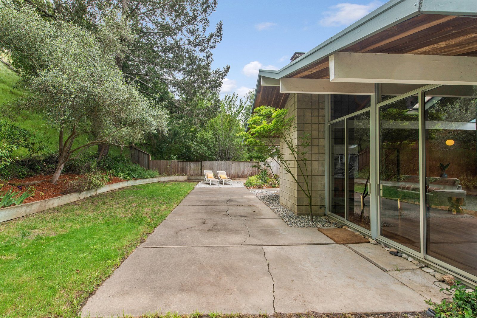 Outdoor, Trees, Concrete Patio, Porch, Deck, Large Patio, Porch, Deck, Back Yard, Grass, Gardens, Horizontal Fences, Wall, and Wood Fences, Wall The backyard has lots of potential for outdoor entertaining.    Photo 12 of 14 in Live Large in This Extra-Spacious Eichler That's Asking $1.38M