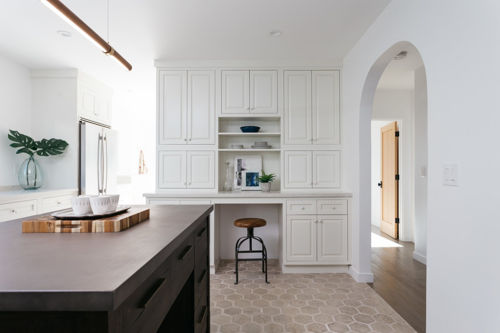 Kitchen, Concrete, Ceramic Tile, Refrigerator, Recessed, Pendant, and White The custom cabinetry includes ample storage and a convenient mini desk.  Best Kitchen Ceramic Tile Pendant Refrigerator Concrete Photos from An Updated Spanish-Style Abode with an Artist Studio Hits the Market at $1.1M in L.A.