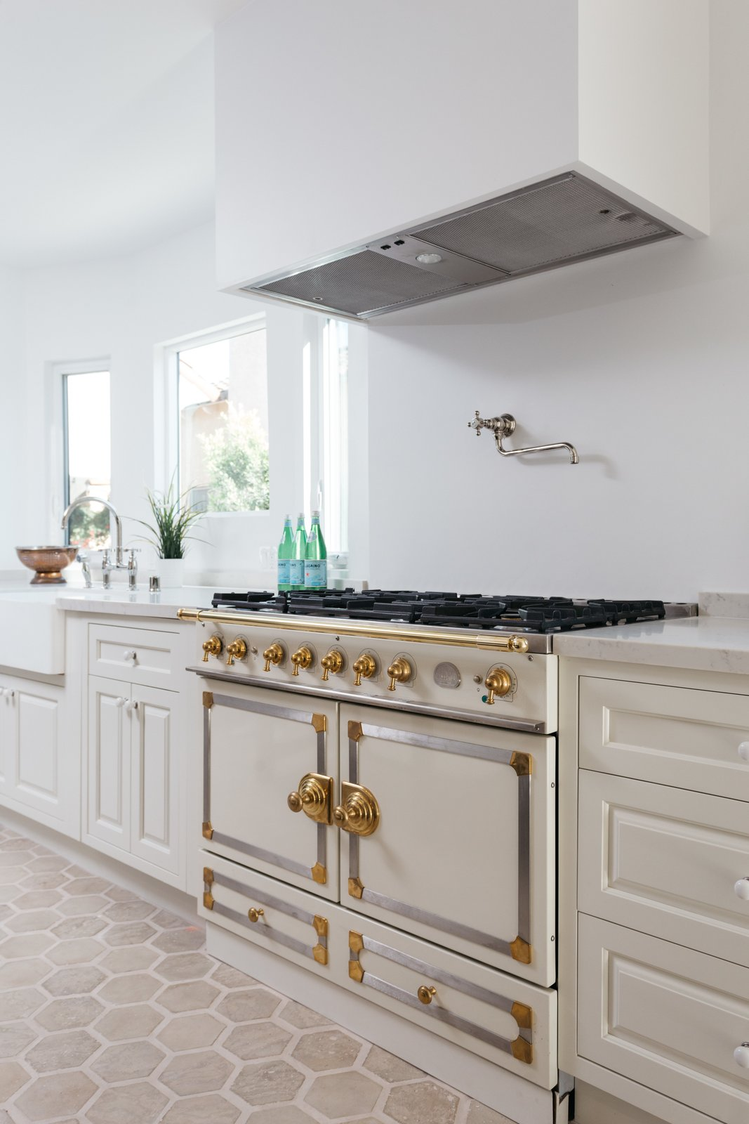 Kitchen, Drop In Sink, Range Hood, White Cabinet, Range, and Ceramic Tile Floor A beautiful La Cornue range is just one of the many high-end upgrades.  Photo 10 of 20 in An Updated Spanish-Style Abode with an Artist Studio Hits the Market at $1.1M in L.A.