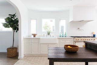 An arched doorway separates the kitchen from the dining room, allowing for easy entertaining.