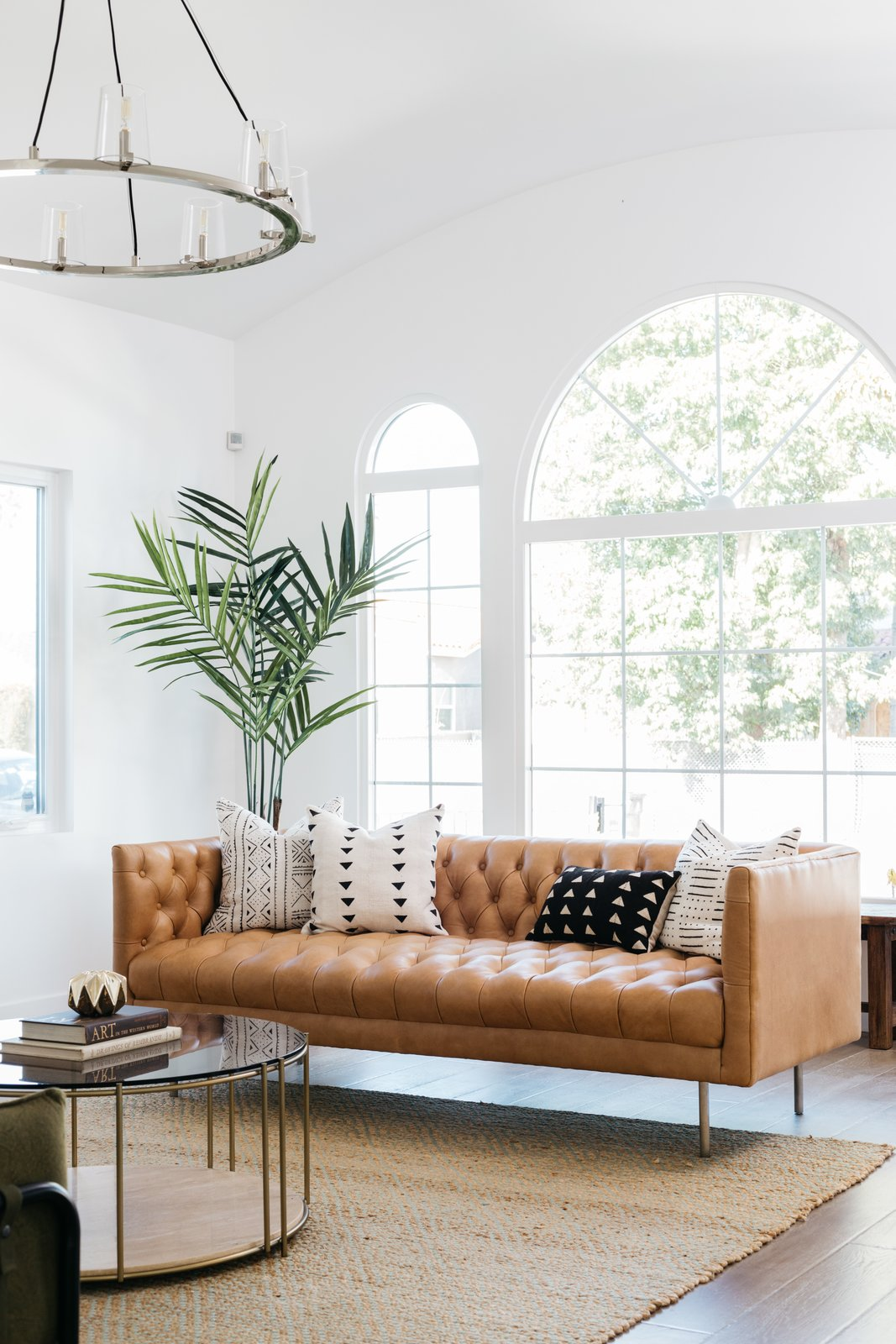 Living Room, Rug Floor, Sofa, Coffee Tables, Medium Hardwood Floor, and Pendant Lighting  The large arched windows allow ample natural light to flood the interiors.     Photo 3 of 20 in An Updated Spanish-Style Abode with an Artist Studio Hits the Market at $1.1M in L.A.
