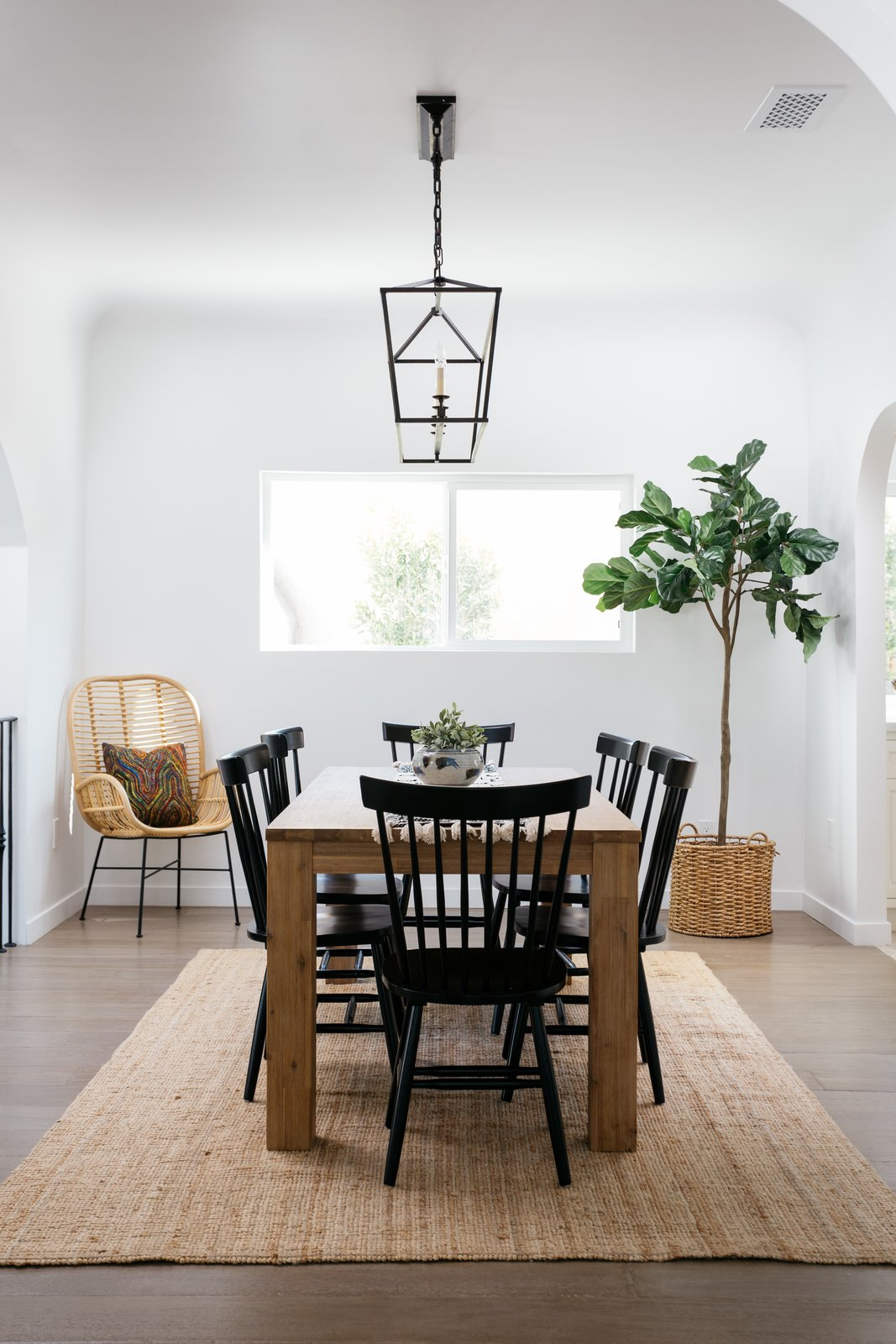 Dining Room, Chair, Pendant Lighting, Medium Hardwood Floor, Table, and Rug Floor The dining room leads to a spacious kitchen.    Photo 7 of 20 in An Updated Spanish-Style Abode with an Artist Studio Hits the Market at $1.1M in L.A.