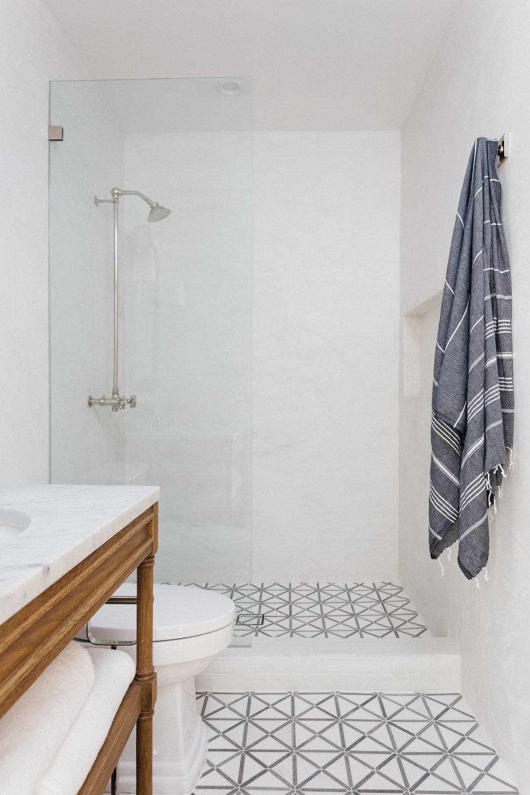 Bath, One Piece, Marble, Porcelain Tile, Open, Recessed, and Undermount The updated bathroom in the hallway has been fitted with geometric floor tiles.     Best Bath Marble Undermount Recessed Photos from An Updated Spanish-Style Abode with an Artist Studio Hits the Market at $1.1M in L.A.