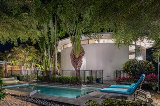 A heated pool is on the second lot and is surrounded by lush tropical greenery.