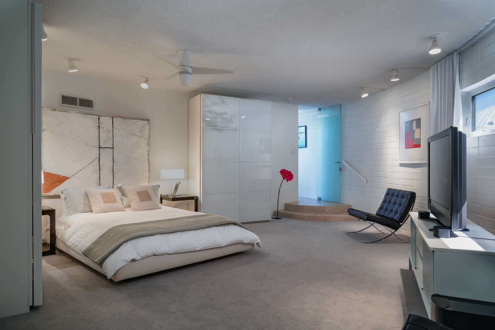 Bedroom, Bed, Ceiling, Carpet, Night Stands, Chair, and Table The master suite features an ensuite bathroom.    Best Bedroom Night Stands Carpet Photos from A Circular Midcentury Gem in Florida Hits the Market at $1M