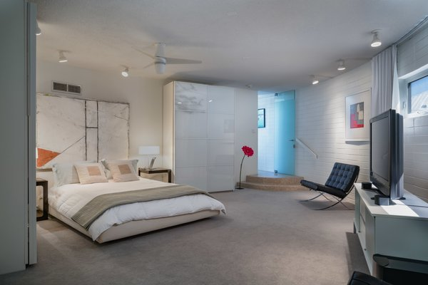 Bedroom, Bed, Ceiling Lighting, Carpet Floor, Night Stands, Chair, and Table Lighting The master suite features an ensuite bathroom.    Best Photos from A Circular Midcentury Gem in Florida Hits the Market at $1M