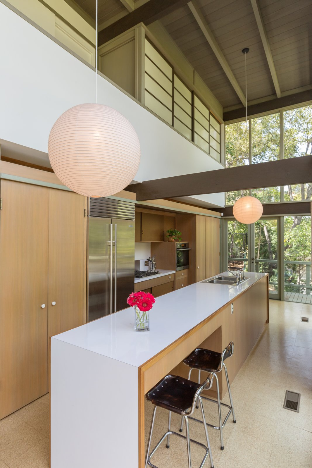 Kitchen, Pendant, Drop In, Laminate, Refrigerator, Wood, Microwave, Cooktops, and Wall Oven The updated kitchen features a Sub-Zero refrigerator and Miele appliances.  Best Kitchen Cooktops Drop In Wall Oven Microwave Laminate Photos from Mad Men Producer Puts His Pasadena Midcentury Up For Auction Starting at $1.7M