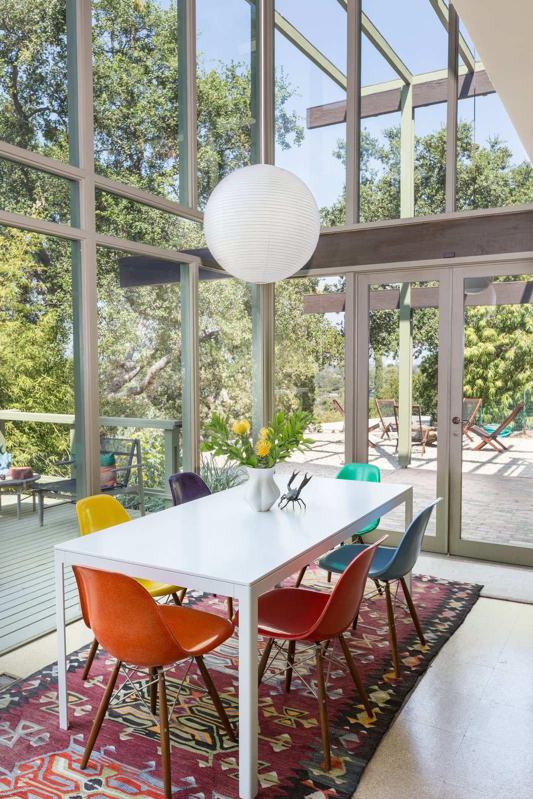 Dining Room, Table, Pendant Lighting, Chair, and Rug Floor Double-height ceilings over the open dining area helps to create a nice, airy vibe.  Best Photos from Mad Men Producer Puts His Pasadena Midcentury Up For Auction Starting at $1.7M