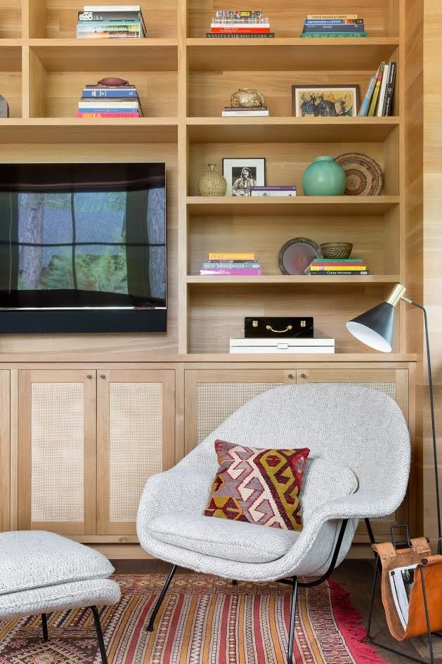 Living Room, Shelves, Rug Floor, Chair, Media Cabinet, Storage, Ottomans, Dark Hardwood Floor, and Floor Lighting A vintage Womb Chair was reupholstered with a nubby custom fabric from Cowtan & Tout. The floor lamp is from Atelier de Troupe, and the rug is a vintage Moroccan flatweave.  Photo 12 of 20 in A Sleek Lake Tahoe Retreat Shows Off an Impressive Art Collection