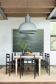 The dining room table is a new, custom-made piece from Nickey Kehoe. It is paired with ebonized black wood chairs with leather sling style seats by Sawkille Co. The chunky braided jute rug with fringe is from Armadillo & Co., the large pendant lights are from Frezoli Lozz, and the artwork is a photograph by Richard Misrach.