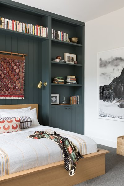 The guest bedroom features custom, built-in shelving over the bed designed by ABD Studio. The bedding is a mix of vintage pillows with Coyuchi. The black and white photograph is from Olivo Barbieri.