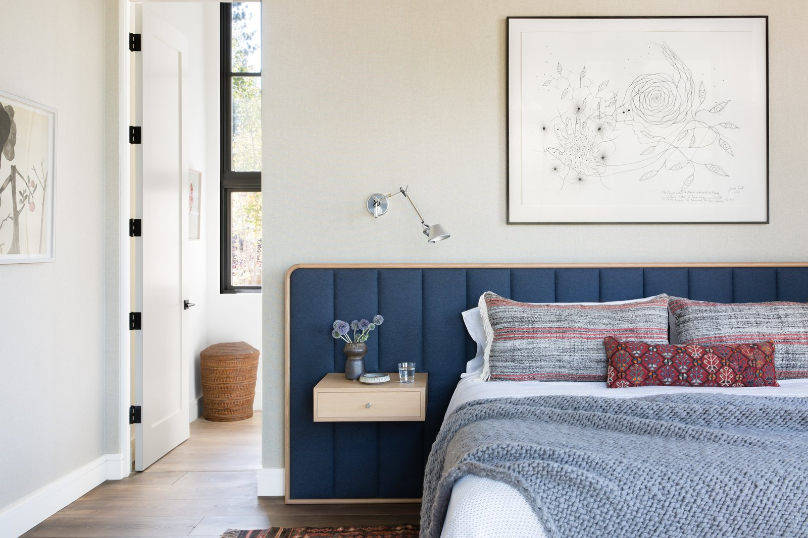 Bedroom, Bed, Medium Hardwood Floor, Wall Lighting, Night Stands, and Rug Floor The custom built-in bed and bedside tables are from ABD Studio. The art above the bed was commissioned from James Surls.   Photo 18 of 20 in A Sleek Lake Tahoe Retreat Shows Off an Impressive Art Collection