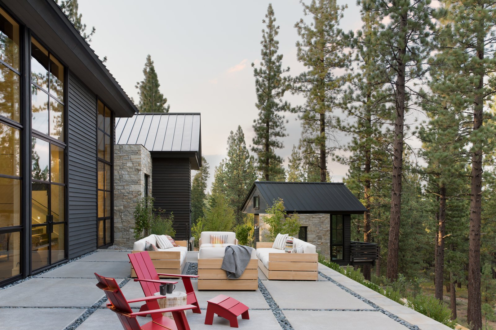 Outdoor, Large Patio, Porch, Deck, Stone Patio, Porch, Deck, Trees, Back Yard, and Concrete Patio, Porch, Deck The home backs on Tahoe National Forest, so the surrounding nature that forms the backyard view will remain unchanged. Concrete slabs with a decorative pebble border form the outside terrace, and the separate structure holds the homeowner's art studio.  Photo 20 of 20 in A Sleek Lake Tahoe Retreat Shows Off an Impressive Art Collection