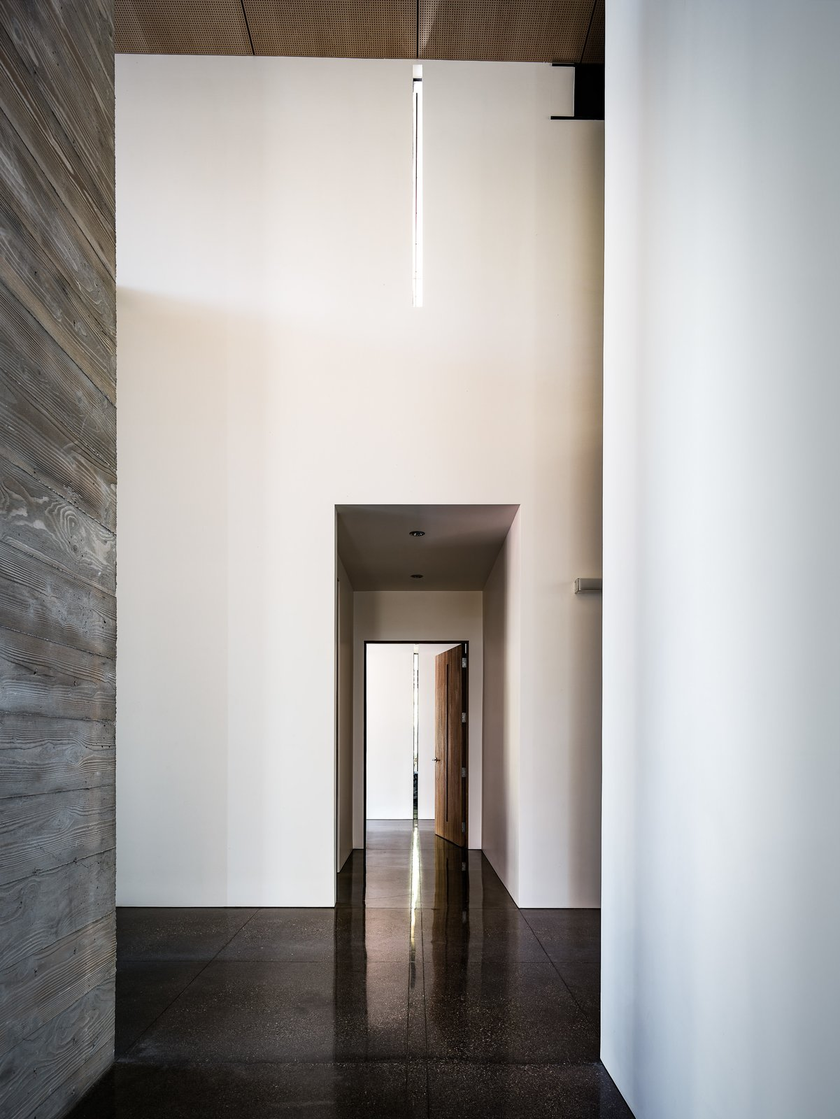 Hallway and Concrete Floor The eye is drawn down the corridor towards the slice of light.  Photo 10 of 18 in An Uplifting Lake Tahoe Retreat Uses Light as a Building Material