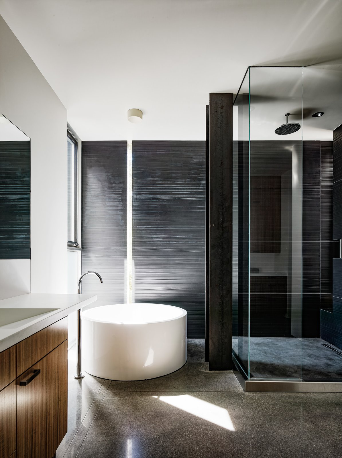 Bath Room, Concrete Floor, Ceiling Lighting, Drop In Sink, Corner Shower, and Soaking Tub Texture, light, and a pureness of materiality turn the bathroom into a balanced composition.  Photo 12 of 18 in An Uplifting Lake Tahoe Retreat Uses Light as a Building Material
