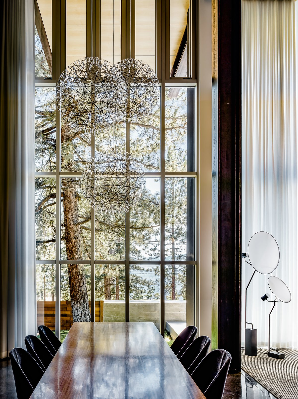 Dining Room, Chair, Pendant Lighting, Table, and Concrete Floor The extensive glazing provides a strong sense of the surrounding nature.  Photo 6 of 18 in An Uplifting Lake Tahoe Retreat Uses Light as a Building Material
