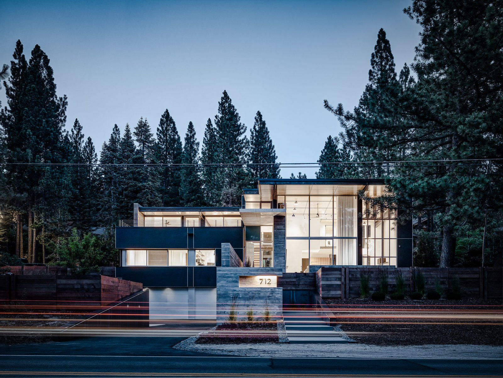 Exterior, Glass Siding Material, Flat RoofLine, Wood Siding Material, Metal Siding Material, House Building Type, and Concrete Siding Material The house is anchored to its sloping site through a series of steps that lead from street-level to front entrance, and through the identification of the garage as a central element of the architecture.  Photo 2 of 18 in An Uplifting Lake Tahoe Retreat Uses Light as a Building Material
