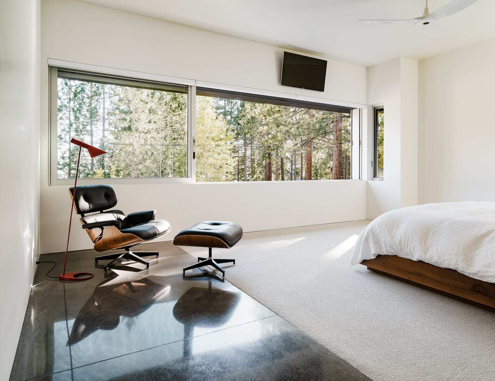 Bedroom, Carpet, Concrete, Bed, Chair, and Floor The window in one of the upstairs bedrooms horizontally frames the view.  Bedroom Concrete Floor Photos from An Uplifting Lake Tahoe Retreat Uses Light as a Building Material