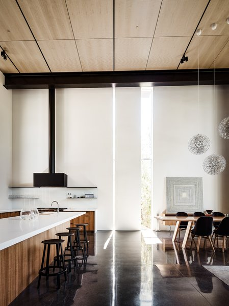 Within the setting of the open floor plan, the slits of light also help demarcate the distinct spaces. Here the kitchen is set off from the dining and living areas.