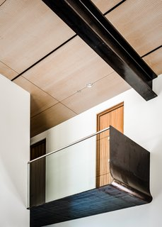 In the main living space, a glass-and-steel bridge is suspended above the kitchen area, becoming a viewport that draws the eye towards the lake.