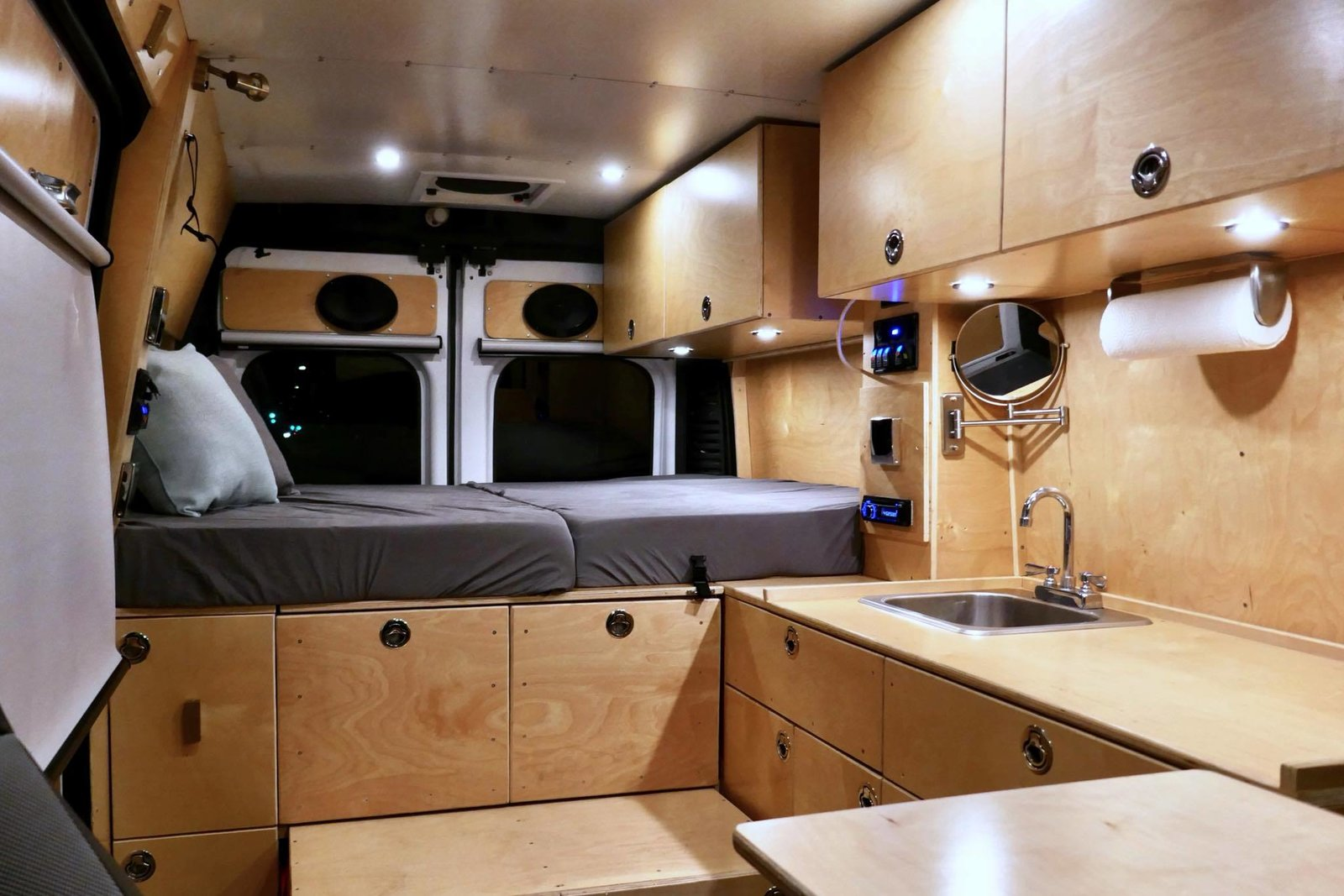 Bedroom, Recessed Lighting, and Bed The beautiful wood interiors have a customized utilitarian feel. The bed in the back can be raised so that the space can also be used as an office.     Photo 2 of 14 in 7 Van Conversion Companies That Will Do the Legwork For You