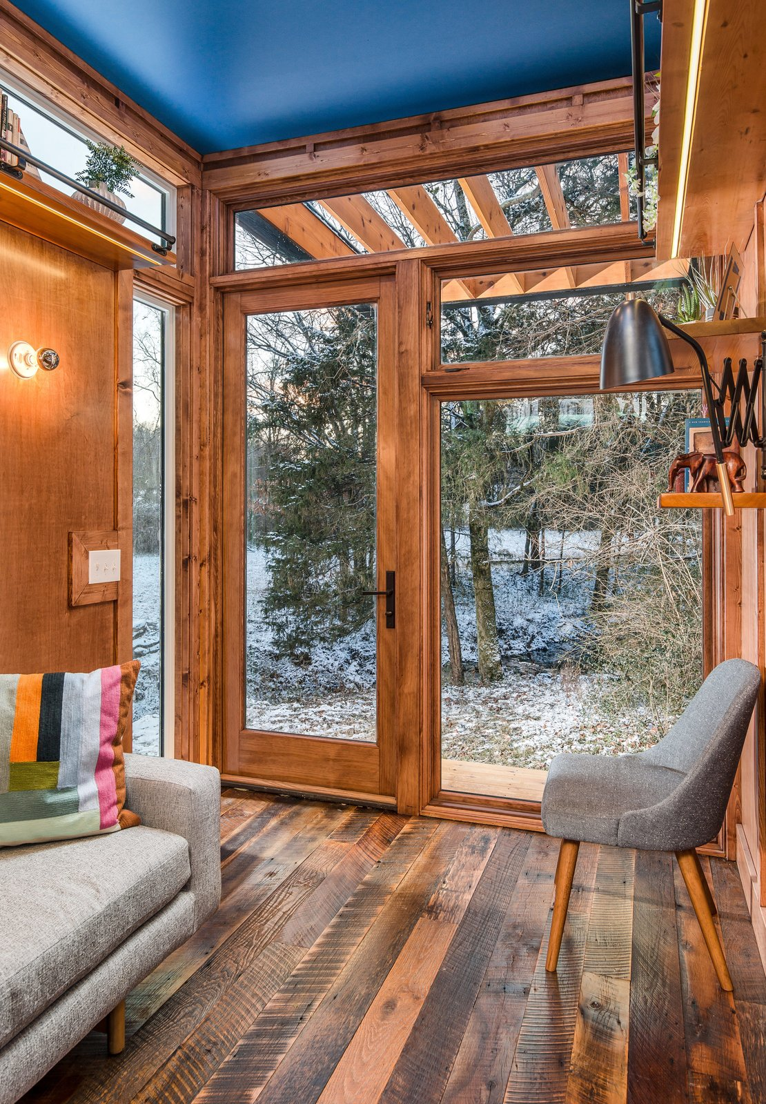 Living Room, Medium Hardwood Floor, Wall Lighting, Chair, Sofa, and Shelves One challenge Latimer faced was that Funke wanted natural light, but also a sense of privacy.  Photo 3 of 12 in This Tiny Home and Writing Studio Was Invented for a Children's Author