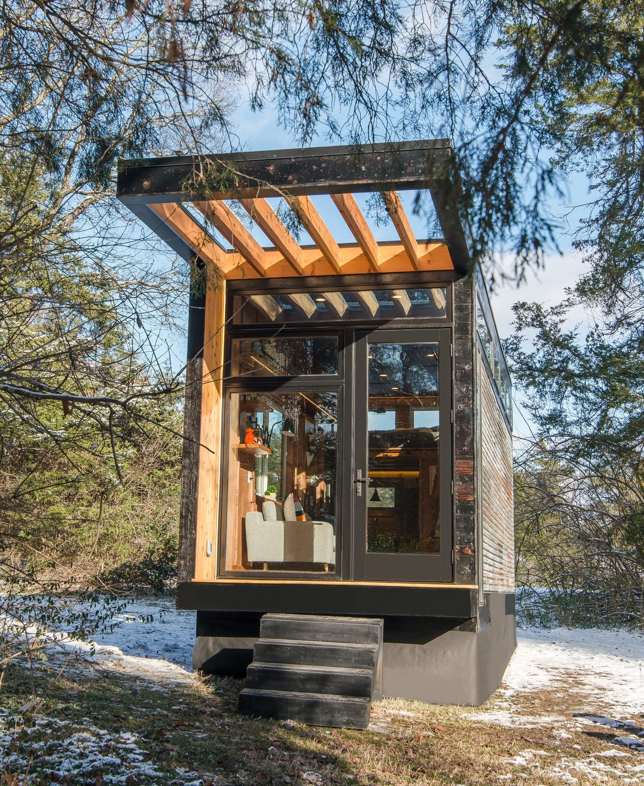 Exterior, Tiny Home Building Type, Glass Siding Material, Metal Siding Material, Wood Siding Material, and Flat RoofLine The tiny home was built on a trailer for easy mobility.  Photo 2 of 12 in This Tiny Home and Writing Studio Was Invented for a Children's Author