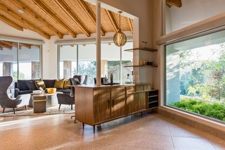 Terrazzo tile floors with solid brass are featured throughout the open plan layout. The cork inserts between the ceiling's vaulted beams were inspired by home's original design.